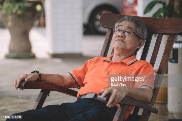 an asian chinese senior man relaxing on his couch in front of his house waiting for his family return home for chinese new year's eve reunion dinner - 70 year old man stock pictures, royalty-free photos & images