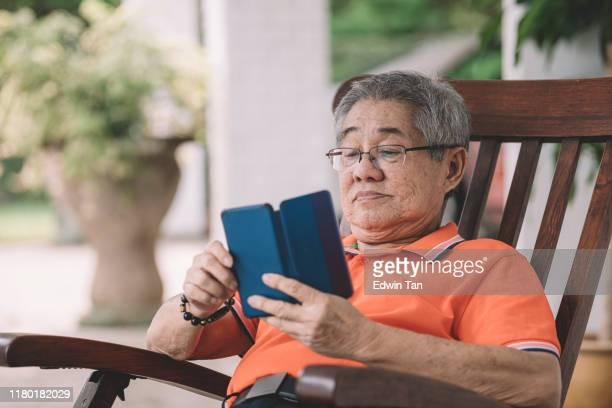 an asian chinese senior man relaxing on his couch in front of his house waiting for his family return home for chinese new year's eve reunion dinner while using his phone for communication - 70 year old man stock pictures, royalty-free photos & images