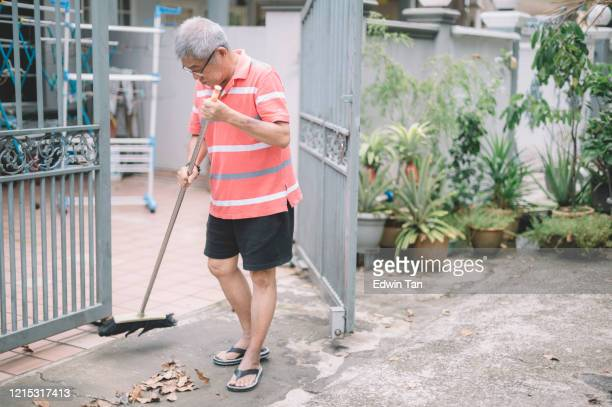 an asian chinese senior man sweeping dry leaves with broom at his front yard during the coronavirus restricted movement order in malaysia - sweeping stock pictures, royalty-free photos & images