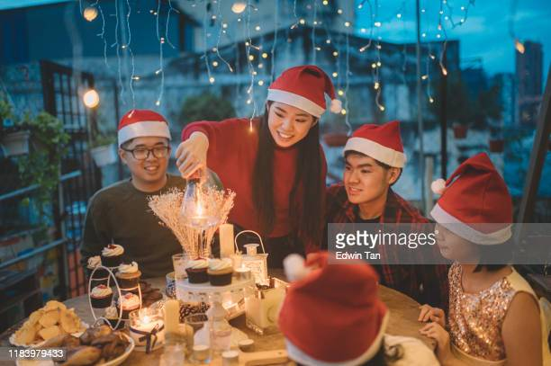 an asian chinese siblings and friends celebrating christmas dinner at front yard of house lighting up candle and setting up table - party host stock pictures, royalty-free photos & images