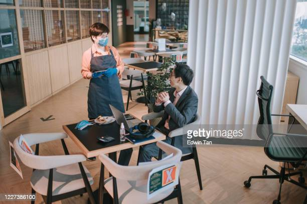 an asian chinese small business cafe owner woman talking to her customer for ordering in the cafe with new normal social distancing standard operating procedure - new normal stock pictures, royalty-free photos & images