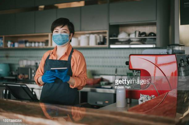 an asian chinese small business owner with face mask and protective gloves hand over the dessert to her customer at kitchen counter smiling looking at camera - essential workers stock pictures, royalty-free photos & images