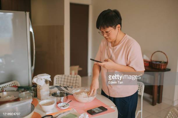 an asian chinese stay home mother preparing dough while using phone online checking for for recipe and guidance online class