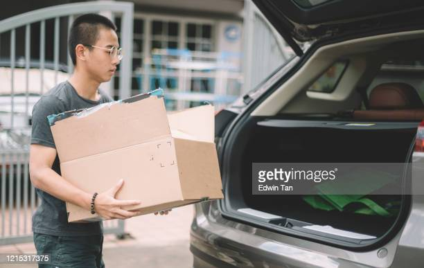 an asian chinese teenager boy carrying a paper box carton to the suv car trunk in front of his house - boot stock pictures, royalty-free photos & images