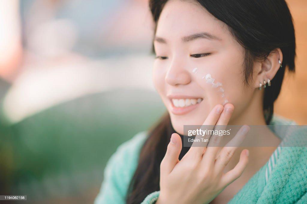 一個亞洲中國青少年女孩應用保濕霜的手和臉 : 圖庫照片