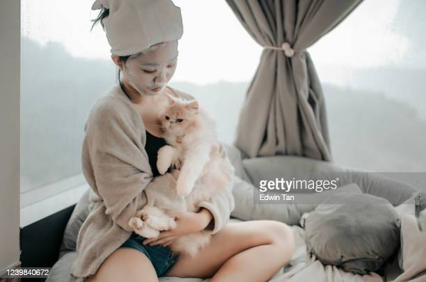 an asian chinese teenager girl  doing face spa mask with her cat in bedroom
