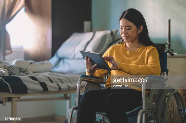 an asian chinese teenager girl on her wheel chair in hospital ward using her digital tablet - persons with disabilities stock pictures, royalty-free photos & images