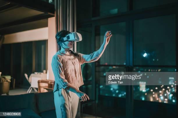 アジアの中国のティーンエイジャーの女の子は、vrゴーグルに置き、リビングルームで3d仮想ゲーム体験を体験 - 仮想空間の視点 ストックフォトと画像