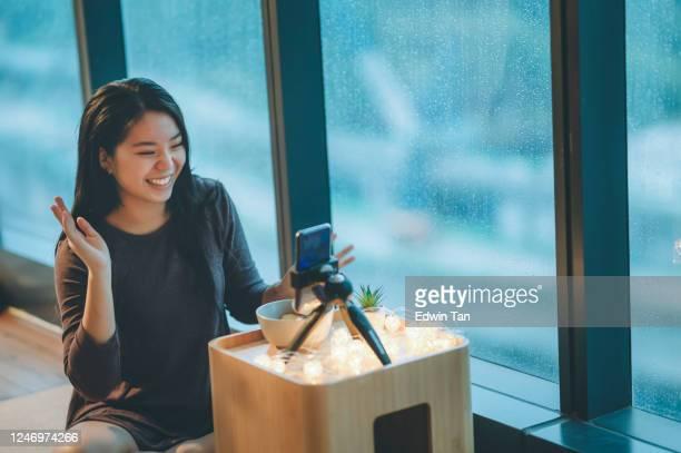 une adolescente chinoise asiatique vlogging dans sa chambre mangeant la pomme utilisant son téléphone intelligent pendant le jour de pluie souriant - influenceur photos et images de collection