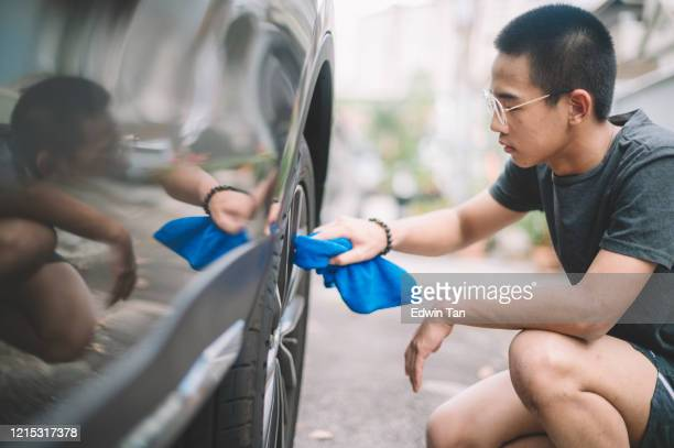 an asian chinese teenager wiping and cleaning car rim at front yard of house during the coronavirus restricted movement order in malaysia - wax stock pictures, royalty-free photos & images