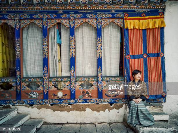 an asian chinese tourist sitting in bhutan temple - paro stock pictures, royalty-free photos & images