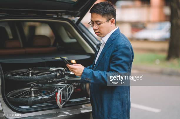 an asian chinese white collar worker executive with folding bicycle for commuting getting it unloading from his car and replying message from his smart phone - foldable stock pictures, royalty-free photos & images