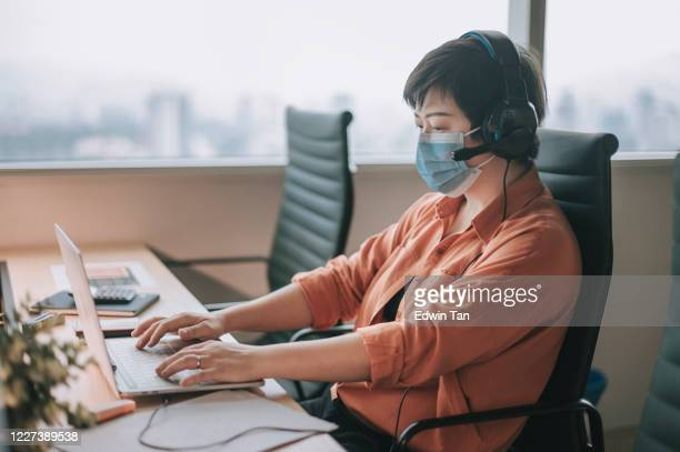 an asian chinese white collar worker woman  back to work after quarantine with new sop and social distancing illness prevention safety precautions - new normal stock pictures, royalty-free photos & images