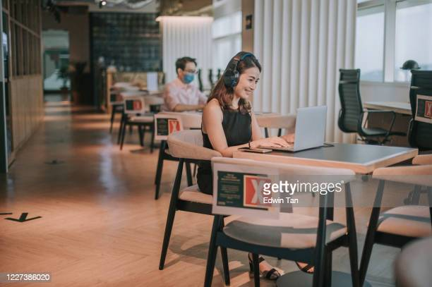 an asian chinese woman freelancer working using laptop in a cafe with face mask listening to phone - hot desking stock pictures, royalty-free photos & images