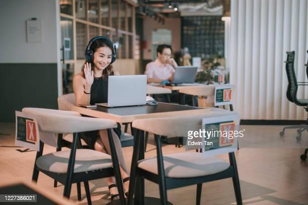 電話を聞いているフェイスマスクを持つカフェでラップトップを使用して働くアジアの中国人女性フリーランサー - コンセプト ニューノーマル ストックフォトと画像