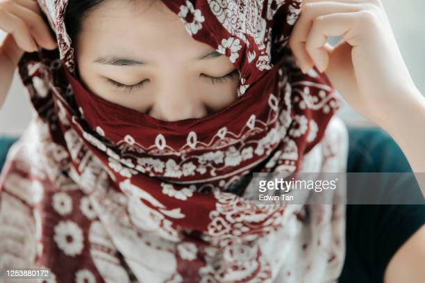 an asian chinese woman portrait headshot with her headscarf covering mouth - charming stock pictures, royalty-free photos & images