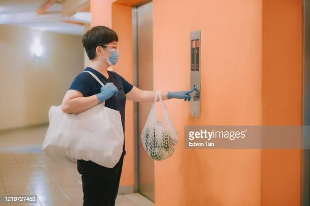 an asian chinese woman pressing the lift elevator button with her reusable bags of groceries