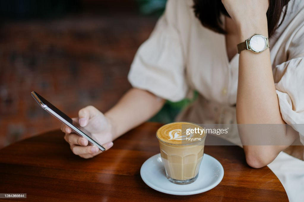 An Asian Chinese woman using smartphone in cafe : Stock Photo