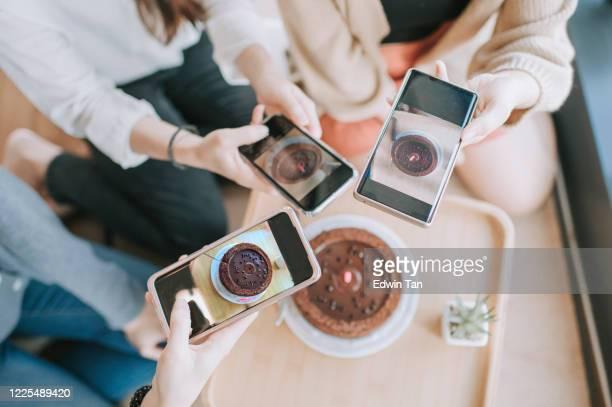 een aziatische chinese jonge mooie vrouw die haar verjaardag met haar vrienden bij haar flat samen met verjaardagscake viert - instagram stockfoto's en -beelden