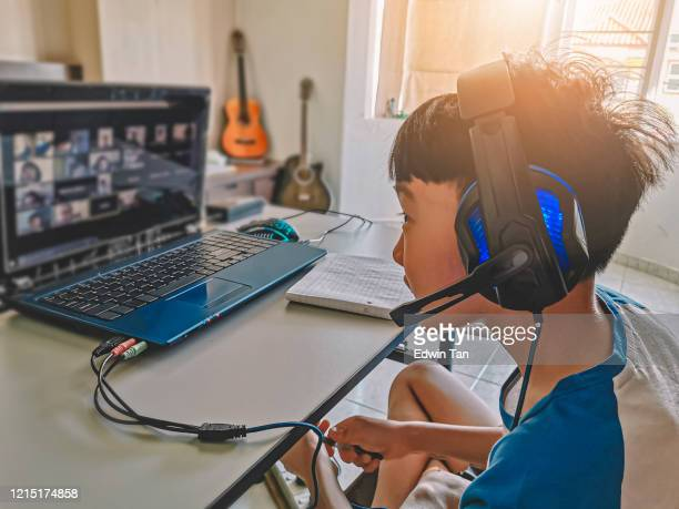 an asian chinese young boy chatting online with all his classmates via online software during restricted movement order period in malaysia - homeschool stock pictures, royalty-free photos & images