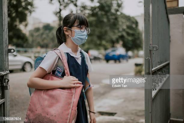 une jeune fille chinoise asiatique revenant de l'école avec le masque facial comme nouvelle normale avec le visage fatigué - écolière photos et images de collection