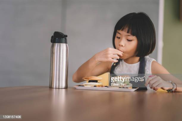 an asian chinese young girl eating and enjoying her home made breakfast pancake with blueberry
