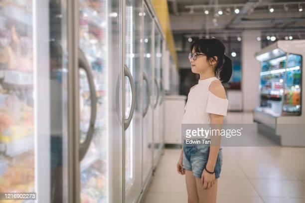 en asiatisk kinesisk ung flicka tittar på den kylda delen väljer för sin glass - china: through the looking glass bildbanksfoton och bilder
