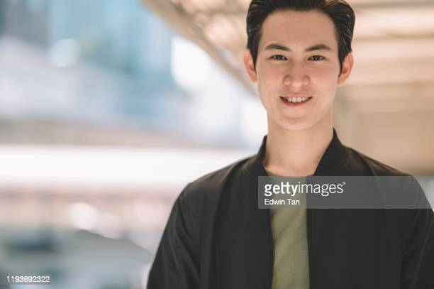 an asian chinese young man looking at camera with his smart casual clothing with jacket at the street of city - south east asia stock pictures, royalty-free photos & images