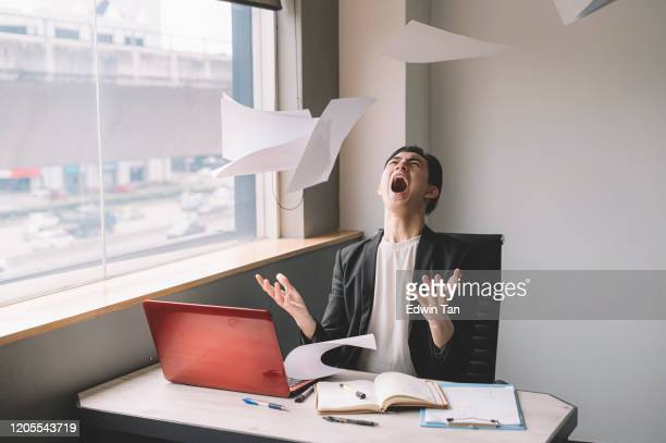 an asian chinese young white collar worker throwing papers in the air frustrated and emotional stress in his office sitting on his chair - arremessar imagens e fotografias de stock