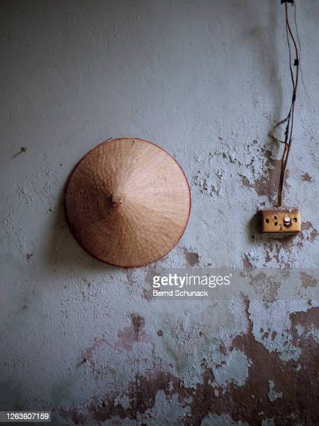 an asian conical hat is hanging on the wall - bernd schunack stock-fotos und bilder
