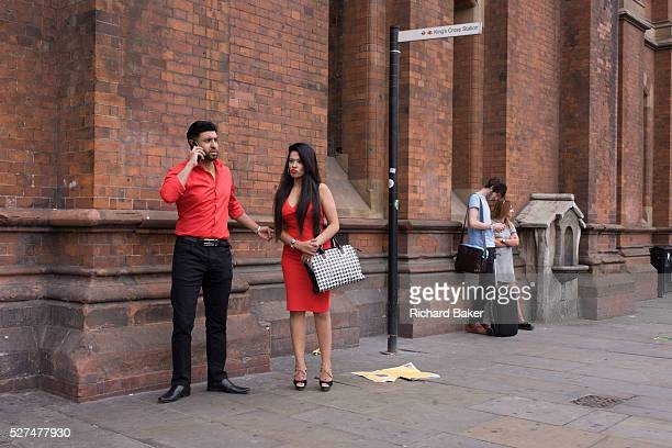 An Asian couple dressed in matching red outside St Pancras station London In conversation on the phone he makes arrangements while his girlfriend...