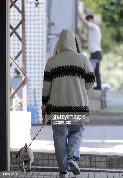 An Asian domestic worker walks her employer's dog in the Lebanese capital of Beirut on April 23 2019 Amnesty International on April 23 urged Lebanon...