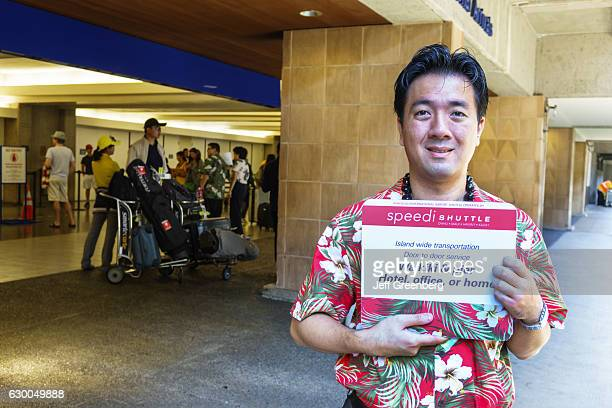 An Asian driver holding a sign at Honolulu International Airport