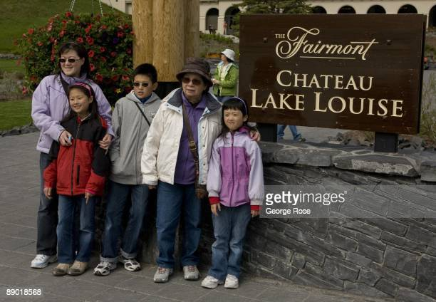An Asian family has their photo taken outside the Fairmont Chateau Hotel in this 2009 Lake Louise Canada summer afternoon landscape photo