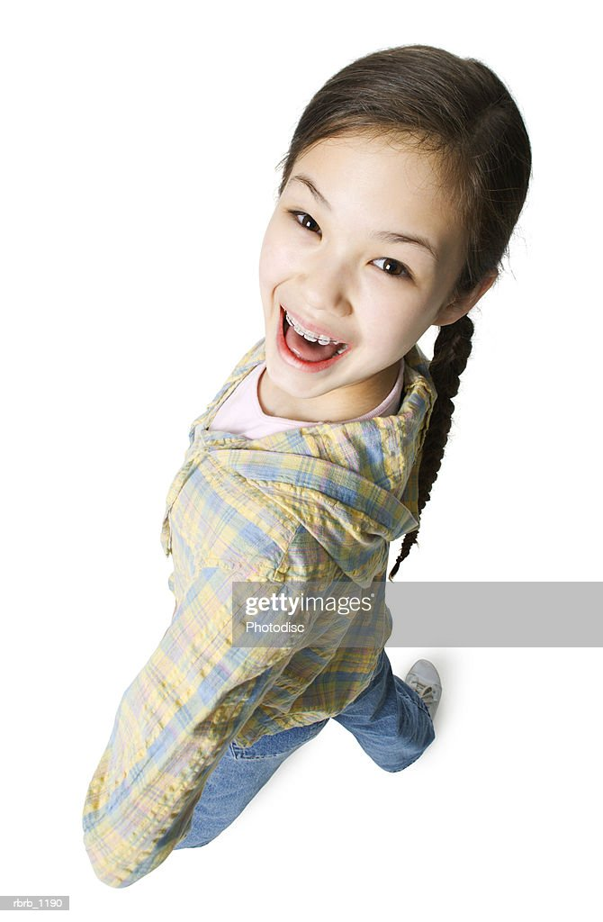 an asian female child in jeans and a green shirt bends around as she smiles up at the camera : Stockfoto