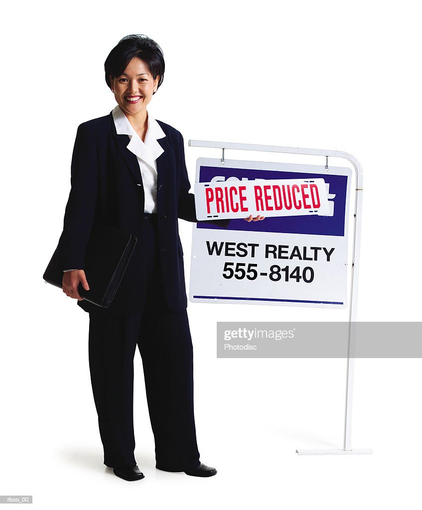 an asian female realator stands smiling by a for sale sign : Foto de stock