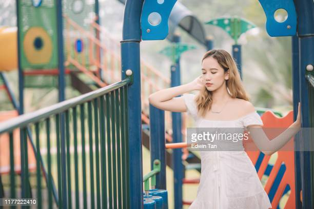 an asian female teenager girl at children playground portrait with dress blonde hair - mini dress stock pictures, royalty-free photos & images