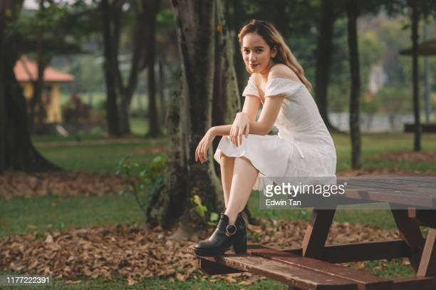 an asian female teenager girl sitting on the park bench portrait - mini dress stock pictures, royalty-free photos & images