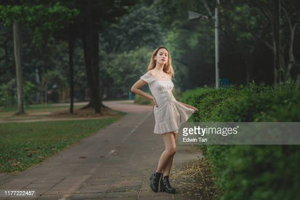 an asian female teenager girl standing at the park looking at camera - mini dress stock pictures, royalty-free photos & images