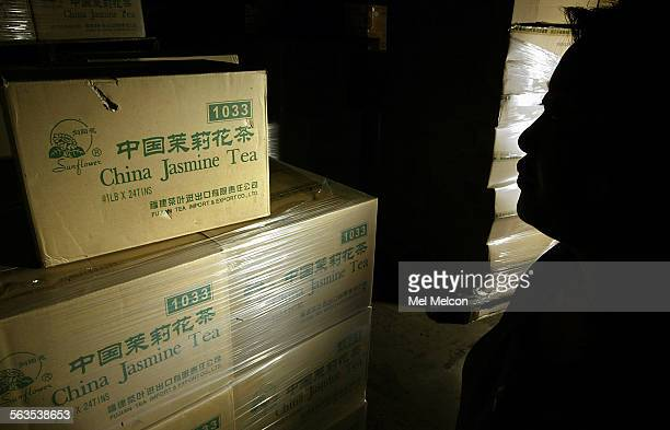 An asian food importer is silhouetted next to some of the 500 cases of China Jasmine Tea that were held up by the FDA for 1 and 1/2 months before...