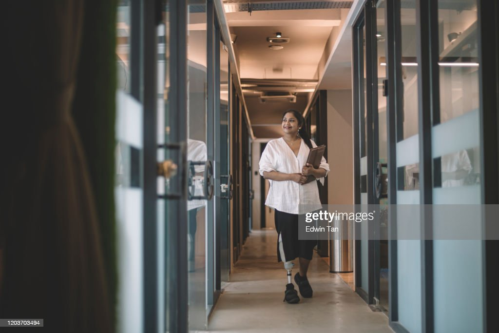 an asian indian female handicapped white collar worker with prosthetic limb  holding her digital tablet and walking at the office corridor smiling : Stock Photo