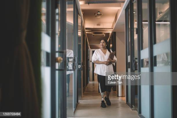 an asian indian female handicapped white collar worker with prosthetic limb  holding her digital tablet and walking at the office corridor smiling - amputee woman stock pictures, royalty-free photos & images