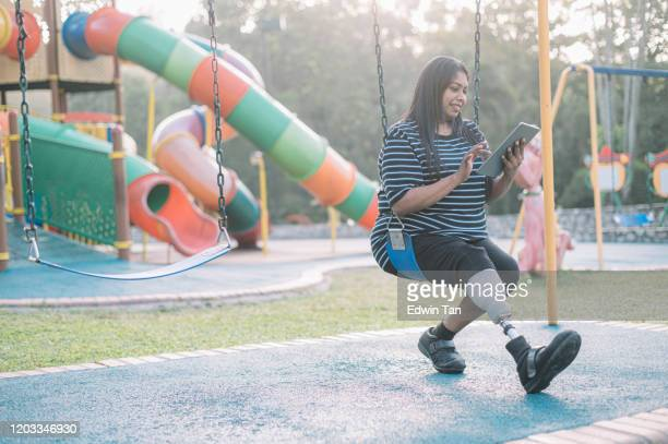 an asian indian female with prosthetic leg in the public park sitting on the swing relaxing - persons with disabilities stock pictures, royalty-free photos & images