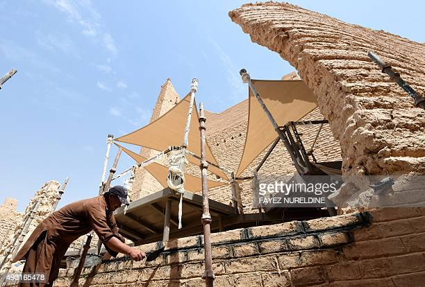 An Asian laborer restores an old building in the historical UNESCO World Heritage Atturaif district on the outskirts of Riyadh on July 13 which is...