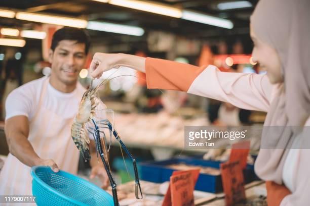 アジアのマレー人女性がトラエビを拾い、湿った市場で魚屋台のベンダーによって与えられたバスケットに入れる - ウシエビ ストックフォトと画像