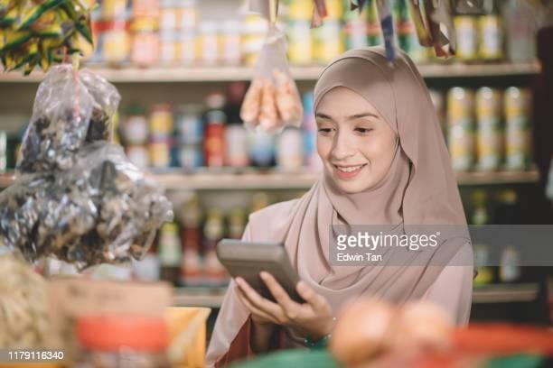 una tienda de comestibles malayo asiático tienda de mujeres propietaria con hiyab calculando el precio del artículo para su cliente - malasia fotografías e imágenes de stock