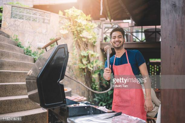 an asian malay male with brace teeth cooking barbecue for his friend at the garden party - apron stock pictures, royalty-free photos & images