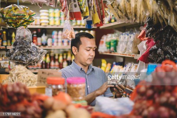 an asian malay mid adult calculating the cost for his customer's selected items - market vendor stock pictures, royalty-free photos & images