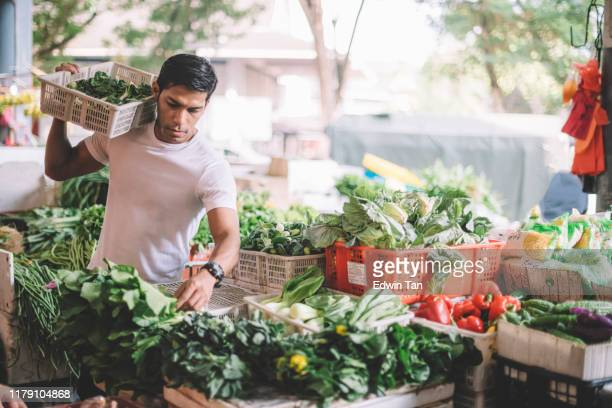 an asian malay vegetable owner arranging vegetables at his stall getting ready for the day - market stall stock pictures, royalty-free photos & images