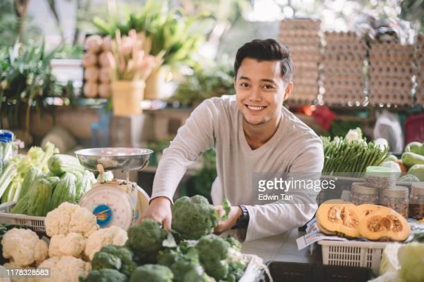 un propietario de verduras de mala y asia organizando sus verduras preparándose para el negocio mirando la cámara - malasia fotografías e imágenes de stock